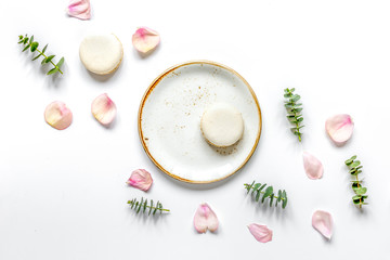 flat lay with petals and macaroons on white background top view