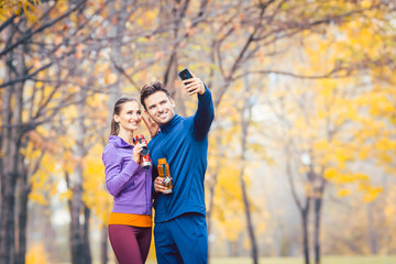 Athletic fitness couple taking selfie photo with their phone for social media
