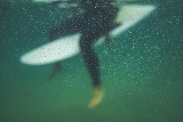 Unfocused underwater view of a surfer seated on his board waiting for a wave surrounded by bubbles