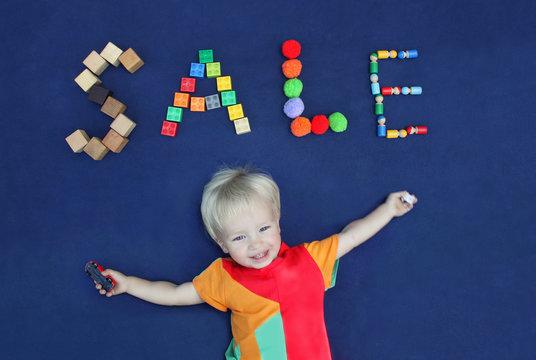 Inscription SALE made from different toys and cute smiling blond boy on blue textile background. Good for baby store