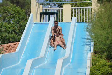 Daddy with kids having fun on slide at waterpark