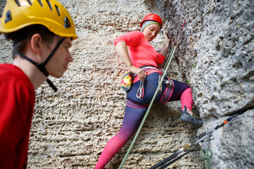 Photo of woman climbing on rock and male instructor