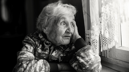 Elderly woman in the house sitting at the table looking out the window. Monochrome photo.