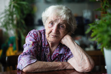 Portrait of an elderly woman sitting in a room at the table.