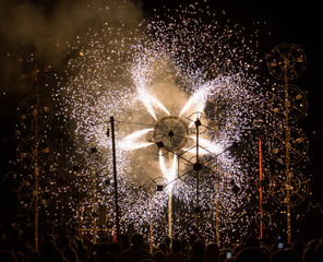 White ground fireworks with a crowd of people watching them during st Anne feast in Malta