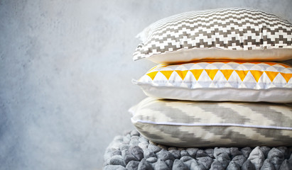 Yellow and grey pillows on the wall background