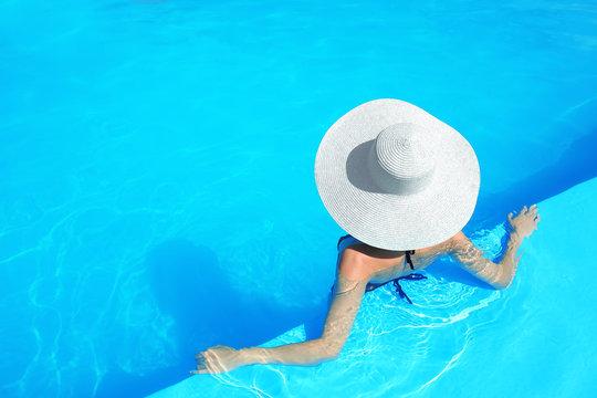 Beautiful young woman resting in swimming pool