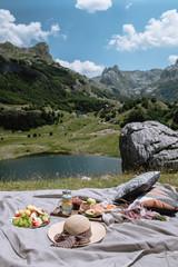 Autocollant pour porte Pique-nique Romantic picnic in the mountains Montenegro. Young woman and man eating Fruit, lemonade and pastries