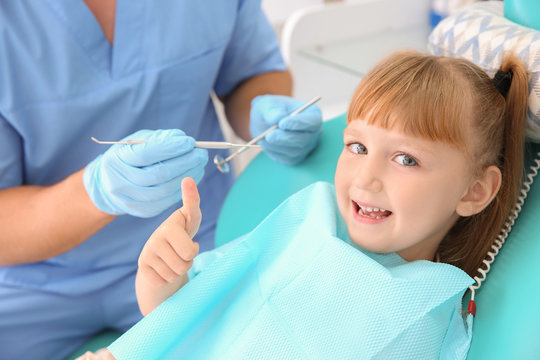 Cute little girl showing thumb-up gesture at dentist's office