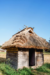 Old wooden shed with thatch roof against blue sky