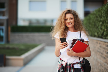 Female student using smartphone outdoor.