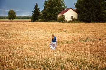 Beautiful blonde girl in a dress in a wheat field.