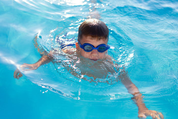 Young boy in goggles swim in swimming pool