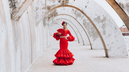 Woman dressed in red dancing flamenco with red fan