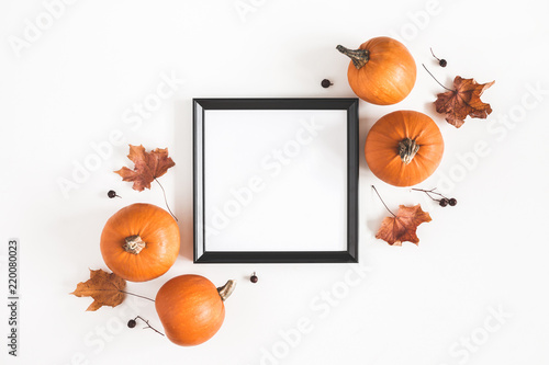 Autumn composition. Photo frame, pumpkins, dried leaves on white background. Autumn, fall, halloween concept. Flat lay, top view, copy space, square