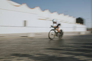 Cyclist going very fast across city street during cycling race. Blurred motion. Fast sensation.
