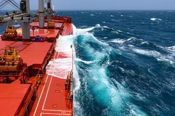 Cargo ship rolling in stormy sea. Huge waves under blue sky in Indian Ocean