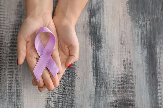 Woman holding lavender ribbon on wooden background. Cancer awareness concept