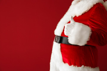 Santa Claus showing thumb-up on color background, closeup