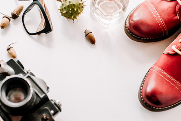 fashion leather shoes for autumn, spring. red boots on a white background lie with the camera, glasses and acorns.