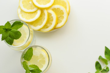 View from above on an arrangement created with refreshing summer drinks in two glasses, plate full of lemon slices and fresh mint leaves, all on white background with copy space.