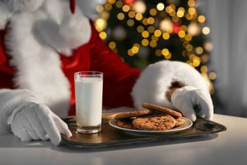 Santa Claus eating cookies and drinking milk at table, closeup
