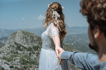 Printed kitchen splashbacks Artist KB Stylish Romantic couple against the background of the mountains. Follow me. Bride holds the bridegroom's hand