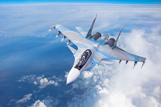 Combat fighter jet on a military mission with weapons - rockets, bombs, weapons on wings flies high in the sky above the clouds.