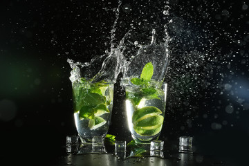 Glasses of fresh mojito with splashes on dark background