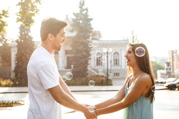 Loving couple walking outdoors while holding hands of each other over soap bubbles.