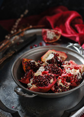 Pieces of pomegranate in a vintage metal bowl on a vintage metal tray. Dark and moody image. Close up