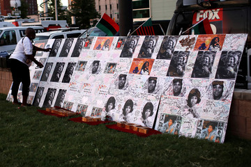 Woman adjusts a board of images and messages for singer Franklin in Detroit