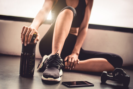 Close up woman exercise workout in indoor fitness gym breaking relax after sport training with dumbbell smart phone and protein shake bottle healthy lifestyle. Athlete and bodybuilder muscles concept.