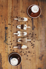 Homemade Espresso Macchiato and Latte Macchiato ice lollies with coffee beans on wooden background