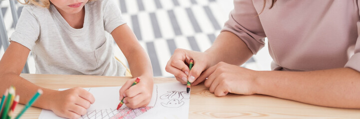 Close-up of kids drawing pictures during art classes at school