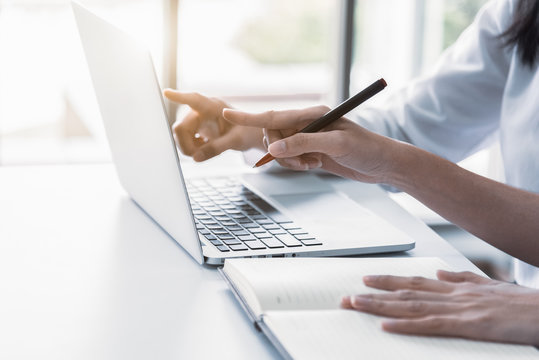 Close up of two businesswoman using laptop and writing on notebook in the morning. Business and financial concept. People and lifestyles concept. Office and workplace theme.