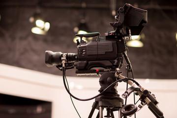 Camera in studio broadcasting news.