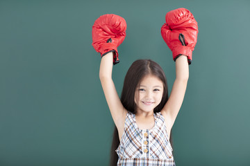 happy little girl with red boxing gloves stand before chalkboard Wall mural