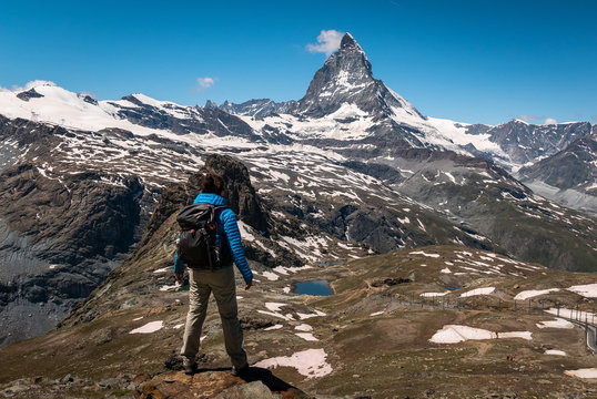 Female traveler with backpack hiking mountain trail and admiring views of Majestic Matterhorn mountain in Valais (Pennine) Alps, Switzerland.