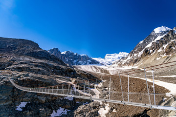 Scenic veiw of hanging bridge over the Glacier de Corbassiere on a mountain trail around Valais Swiss Alps.