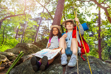 Kids rest during hike boy and girl with map