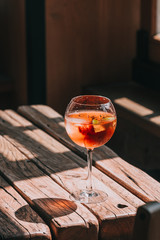 Aperol Spritz in wine glass on wooden table at the restaurant. Food photography. Direct sunlight, copyspace