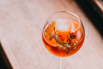 Aperol Spritz in wine glass on wooden table at the restaurant. Food photography, copyspace, minimalism