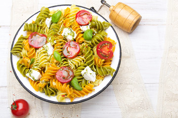 Kuchnia włoska - Sałatka z kolorowego makaronu, pomidorów koktajlowych, sera feta i świeżej bazylii na białym drewnianym tle.