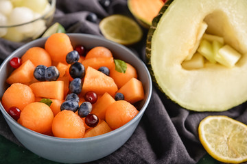 Bowl with delicious melon balls and berries on table, closeup
