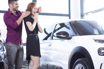 Handsome husband surprising his wife with a car purchase