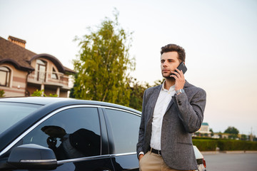 Photo of successful business man wearing suit, standing near his luxury black car and talking on smartphone