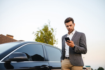 Portrait of rich businessman wearing suit, standing near his luxury black car, and using smartphone while holding in hand