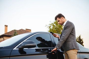 Portrait of caucasian businessman wearing suit, opening driver's door of his luxury black car, and using smartphone