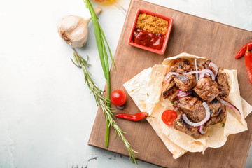 Board with delicious shish kebab and sauce on light table